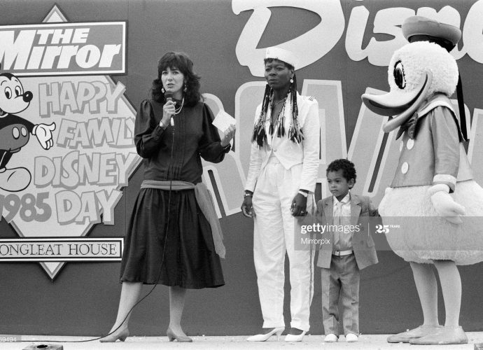 Ghislaine Maxwell standing on stage with a child and Donald Duck at the 1985 Happy Family Disney Day.